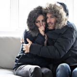 Bundled up couple inside trying to keep warm because their heater is blowing cold air